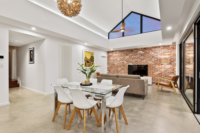 brick accent wall, glass table, white chairs, vaulted ceiling beams, grey sofa, white walls, tall sliding doors
