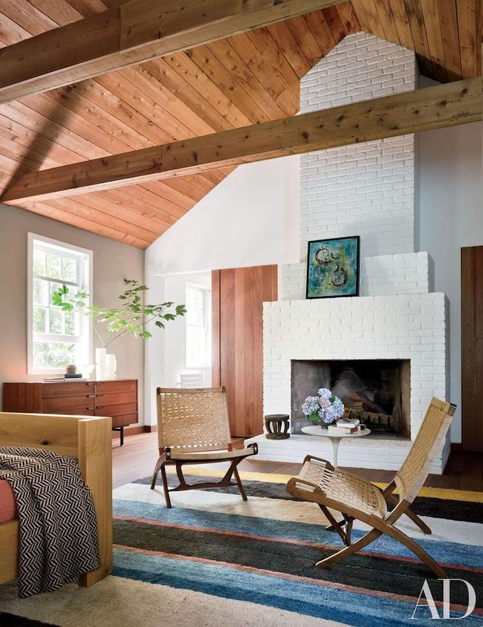 cathedral ceiling, white brick fireplace wall, blue and white carpet, wooden ceiling, white walls, wooden chairs