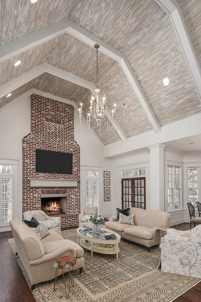 brick fireplace wall, vaulted ceiling ideas, white sofas, wooden floor, throw pillows, hanging chandelier