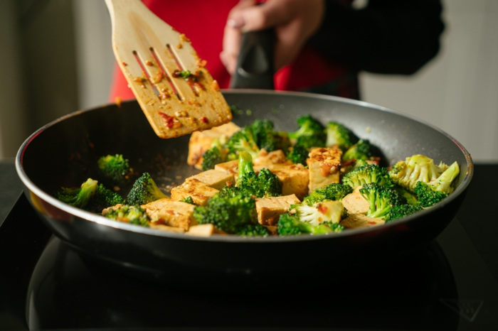tofu in sauce and broccoli, cooked in black sauce pan, stirred with wooden spatula, asian tofu