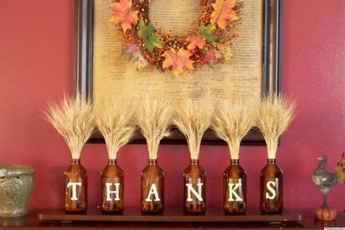 brown bottles, wheat inside, arranged on mantel, thanks written on them, turkey decoration, red wall, fall leaves wreath