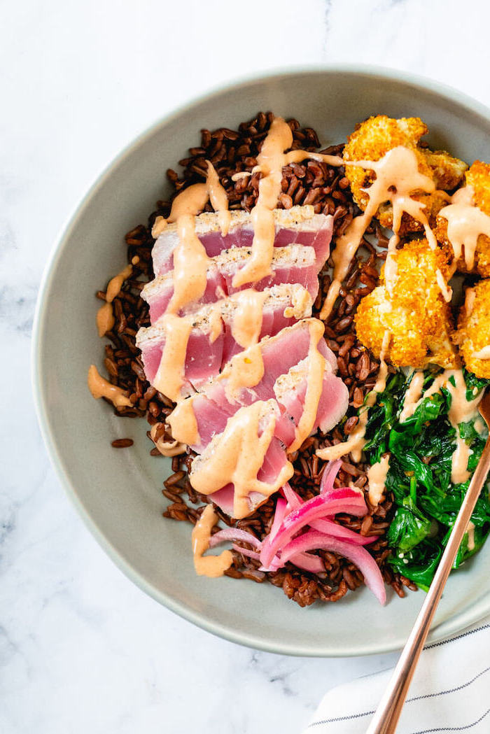 easy dinner recipes for two, tuna slices, brown rice, with spinach, in a white bowl, marble countertop