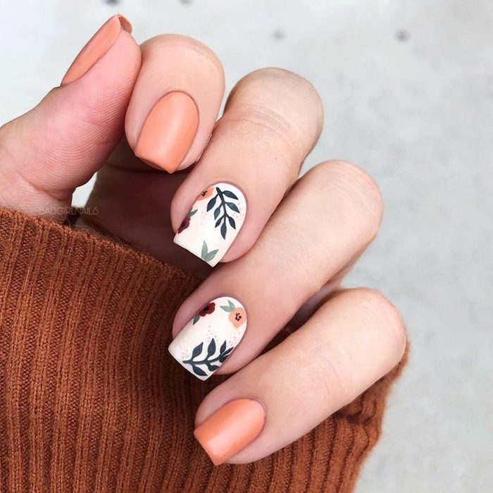 orange and white nail polish, fall nail designs, floral design, short square nails, brown sweater, white background