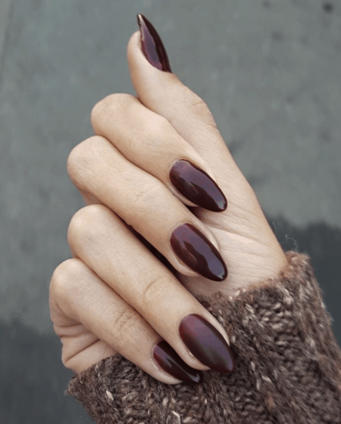 almond nails, trending nail colors, burgundy red, nail polish, brown sweater, blurred background