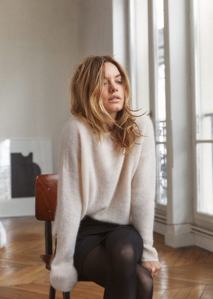 camille rowe sitting on a chair, wearing white sweater and black skirt, medium haircuts for women, wooden floor, white walls