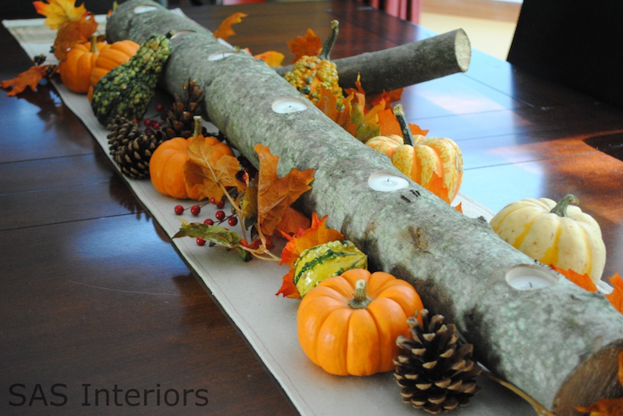 wooden log, candles inside, autumn decor, small pumpkins, pine cones, fall leaves, arranged as table runner