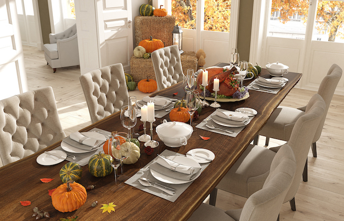 wooden table, white chairs, fall decor, pumpkins scattered around, wine glasses, candles and leaves
