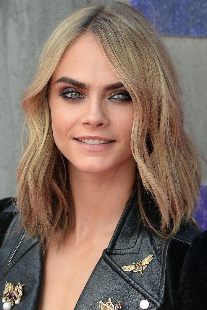 cara delevingne smiling, wearing black leather jacket, with blonde wavy hair, medium length hairstyles