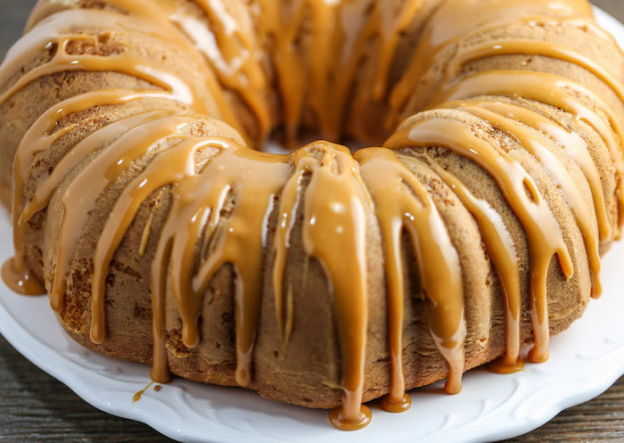 bundt cake, chocolate thanksgiving desserts, caramel drizzle on top, white plate, wooden table