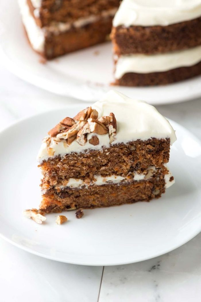 carrot cake, white frosting, crushed walnuts on top, thanksgiving desserts, white plate, marble countertop