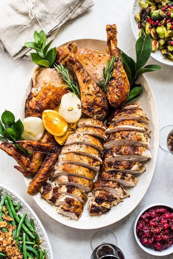 how long to bake a turkey, carved turkey, lemon slices, fresh herbs, on the side, white table, white plate