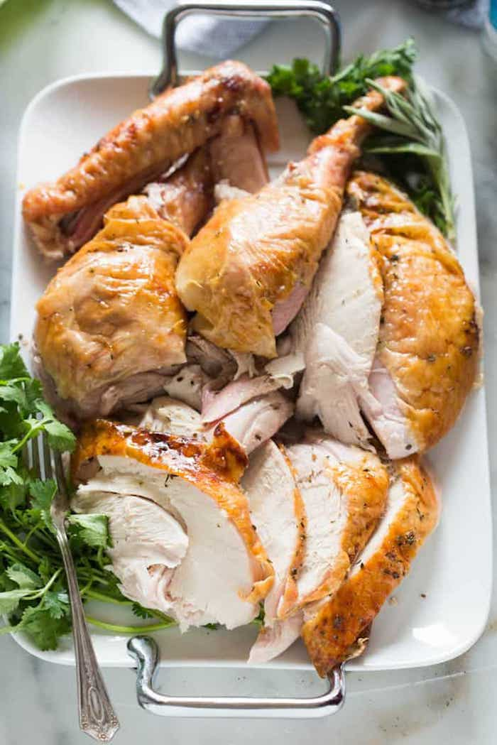 how long does it take to cook a turkey, carved turkey, fresh herbs on the side, white plate, silver fork