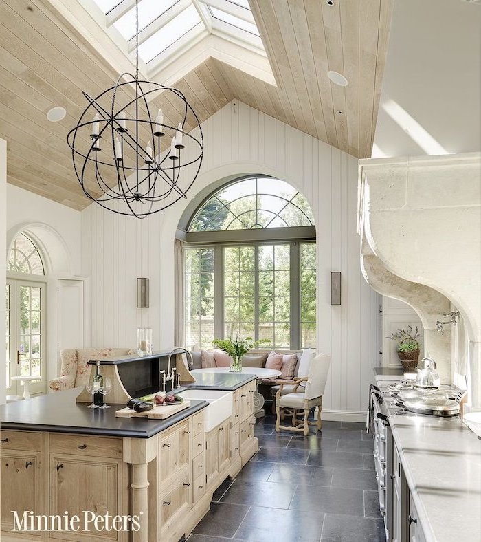 wooden ceiling with skylights, vaulted ceiling ideas, tiled floor, wooden kitchen island, white walls, rustic decor