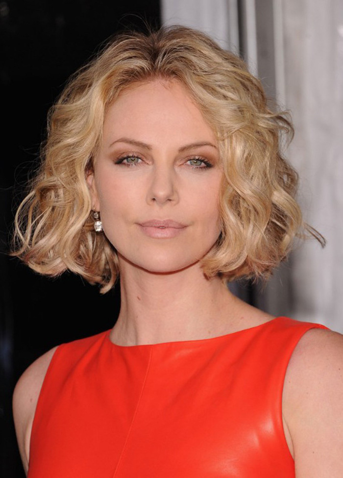 charlize theron, wearing red leather dress, blonde curly hair, shoulder length layered hair, small earrings