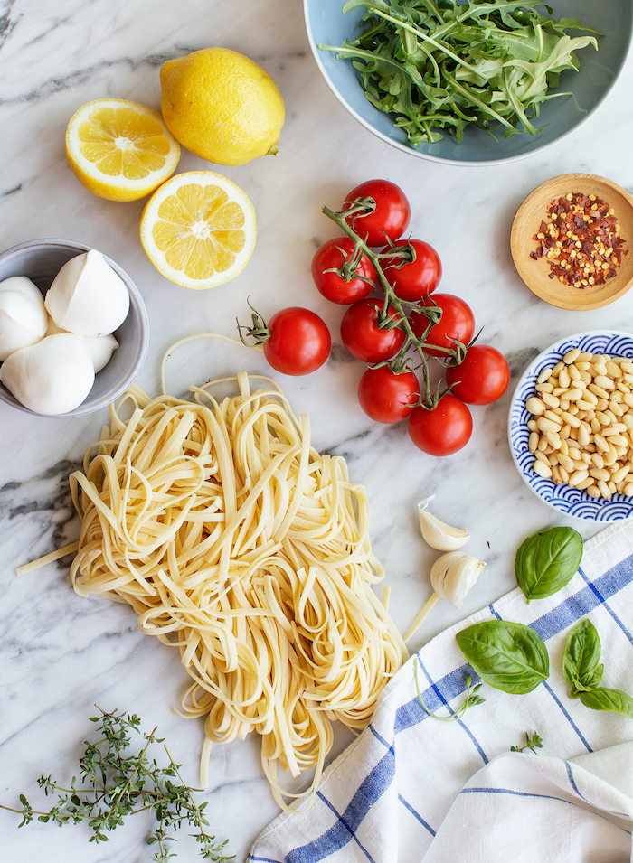 easy dinner ideas, pasta and garlic, basil leaves, cherry tomatoes, lemon slices, bowls full of ingredients, on marble table,