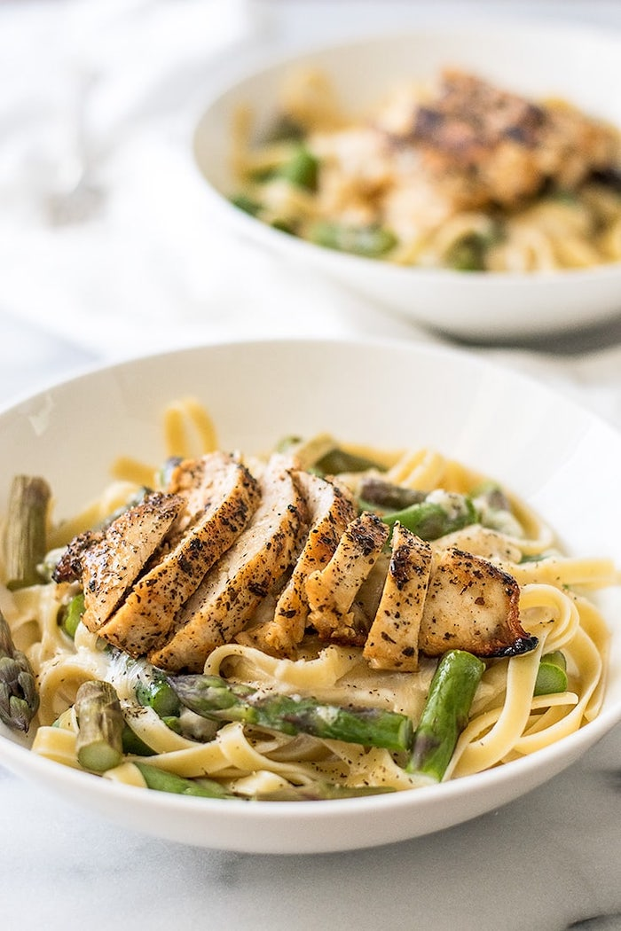 chicken breast, on top of pasta with asparagus, in white bowl, easy dinner recipes for two, marble countertop