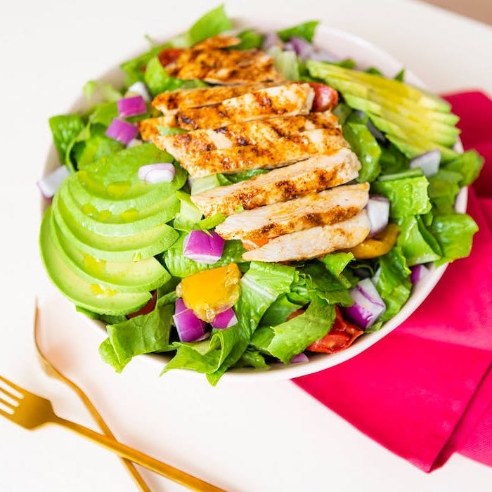 sliced chicken breast, on top of green salad, with avocado slices, red cloth, white plate, meal prep for weight loss
