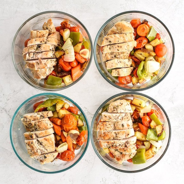 four glass containers, baked veggies, sliced chicken breasts inside, meal prep for weight loss, white table