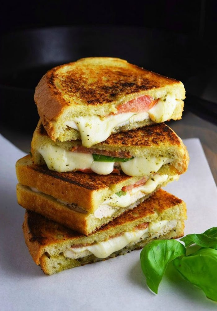 grilled cheese sandwich, chicken pesto panini, easy healthy dinner ideas, white plate, basil leaves on the side