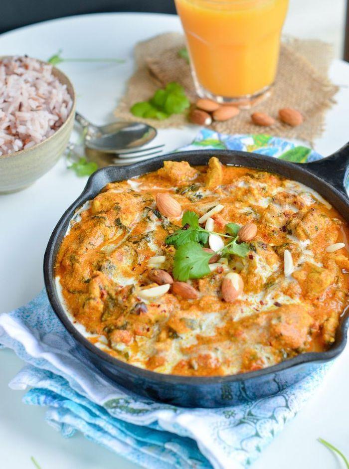 chicken tikka masala, black skillet, orange juice, best weight loss diet, blue cloth, almond and parsley garnish