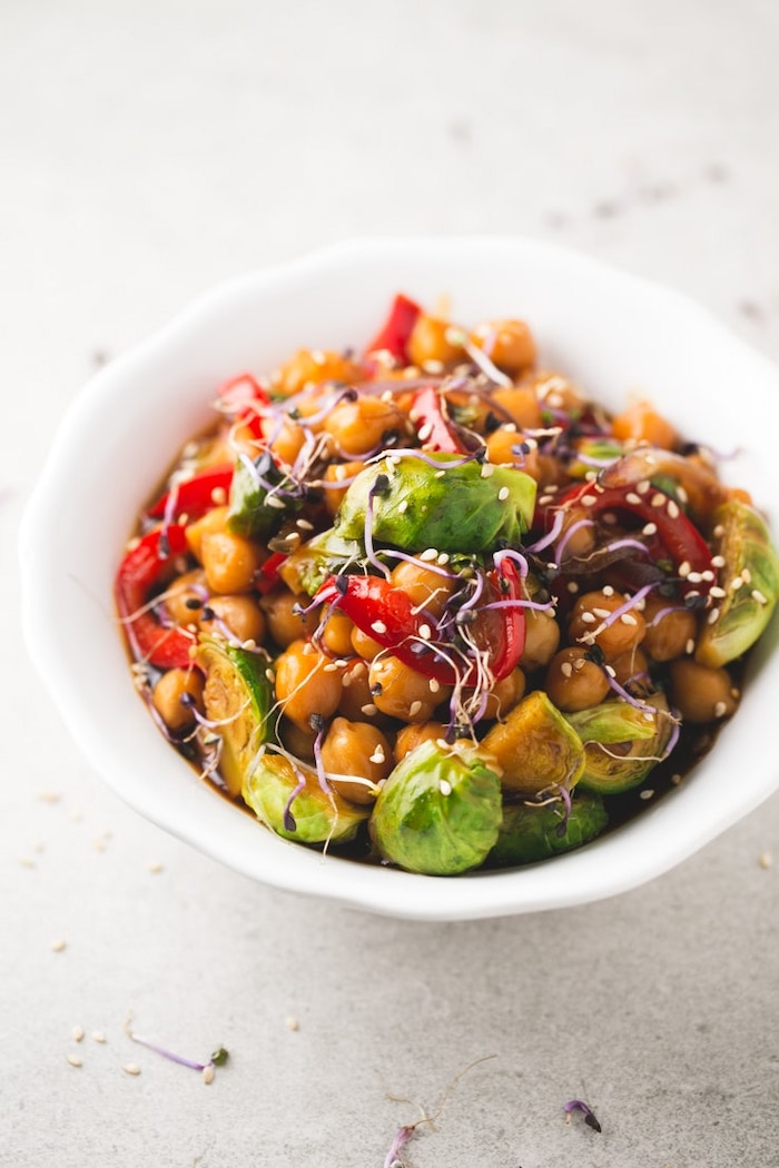 chickpea and vegetables stir fry, with sesame seeds, in white ceramic bowl, healthy dinner ideas, white table