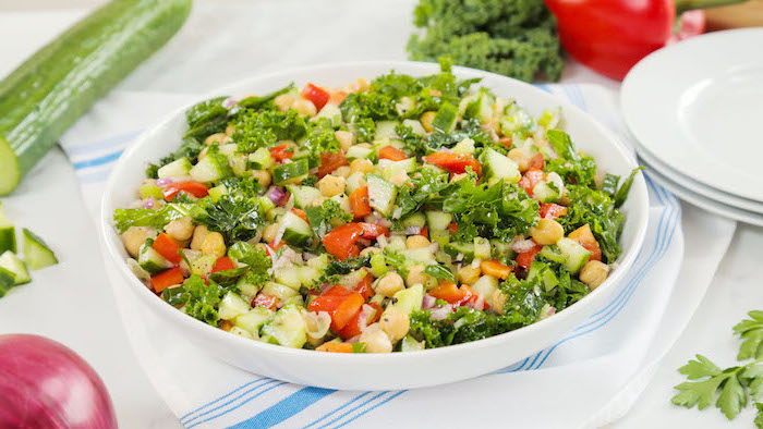 chickpea salad, healthy meal prep ideas, cucumbers and tomatoes, onion and parsley, in white plate