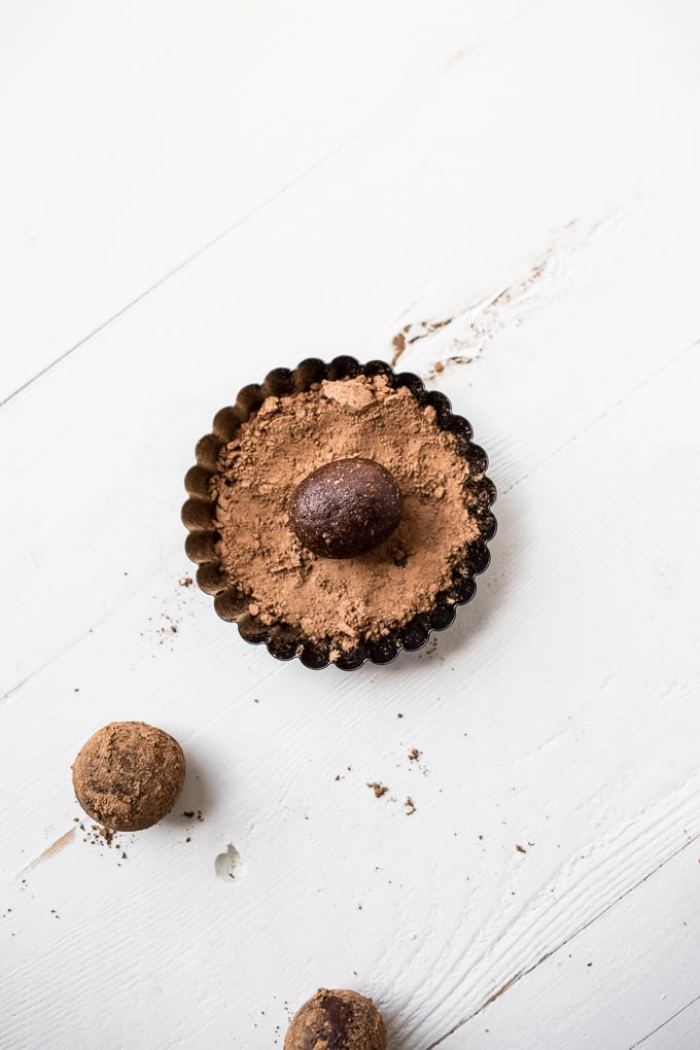 cocoa powder, in a brown ball, healthy peanut butter balls, white wooden table