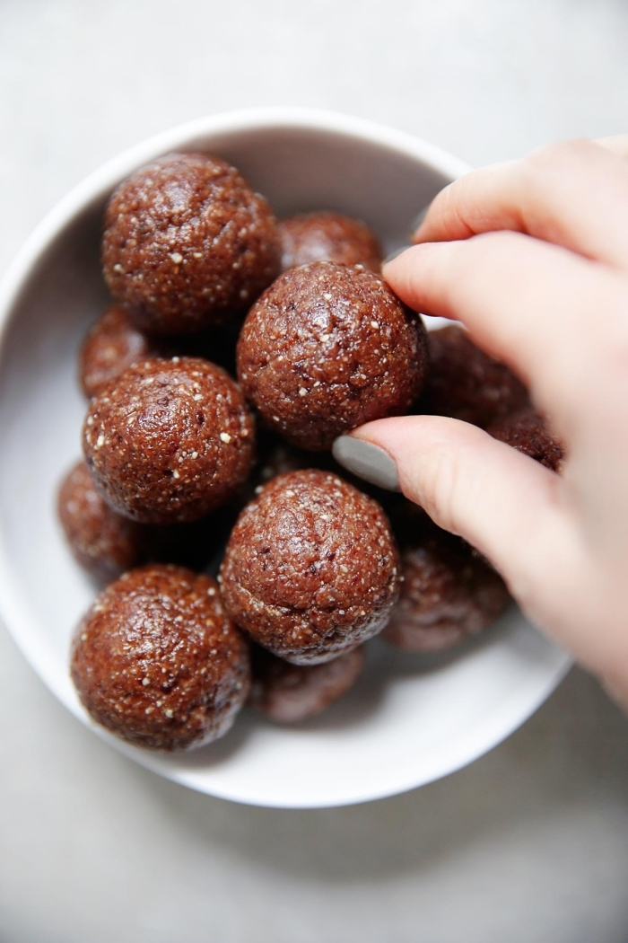peanut butter energy balls, chocolate truffles, in a white bowl, female hand, with grey nail polish, white table