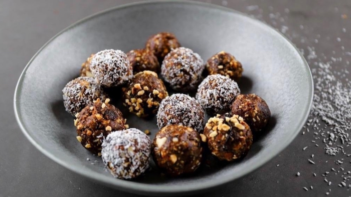 healthy peanut butter balls, covered in nuts, coconut flakes, in grey bowl, coconut flakes, scattered on the table