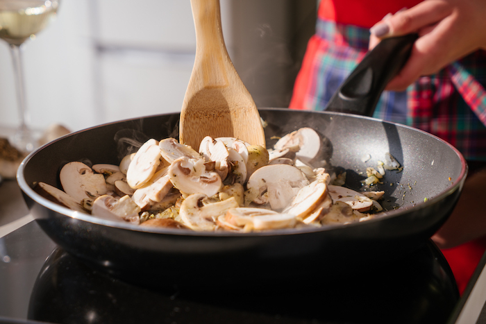mushrooms stirred with onion, in black sauce pan with wooden spoon, mushroom risotto recipe, blurred background