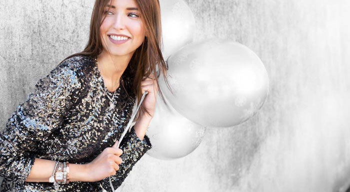 woman holding three balloons, wearing black sequinned dress, lots of bracelets, christmas gift ideas