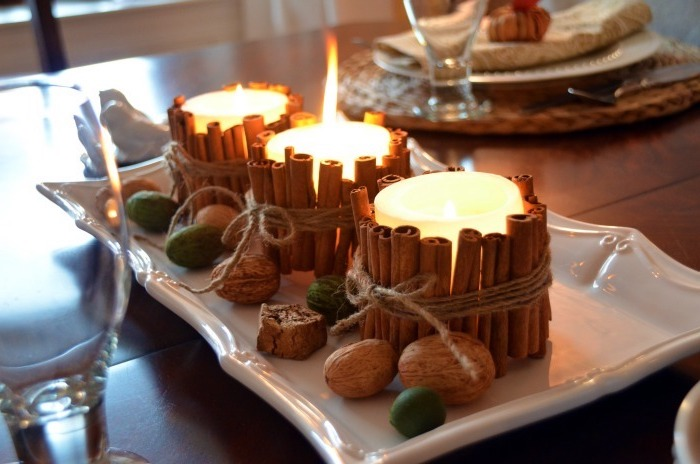 candles with cinnamon sticks, tied with twig, around them, arranged on white plate, thanksgiving decorating ideas, walnuts scattered