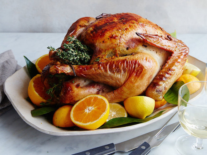 white plate, how long to bake a turkey, roasted turkey, fresh herbs, lemon slices, on the side, wine glass