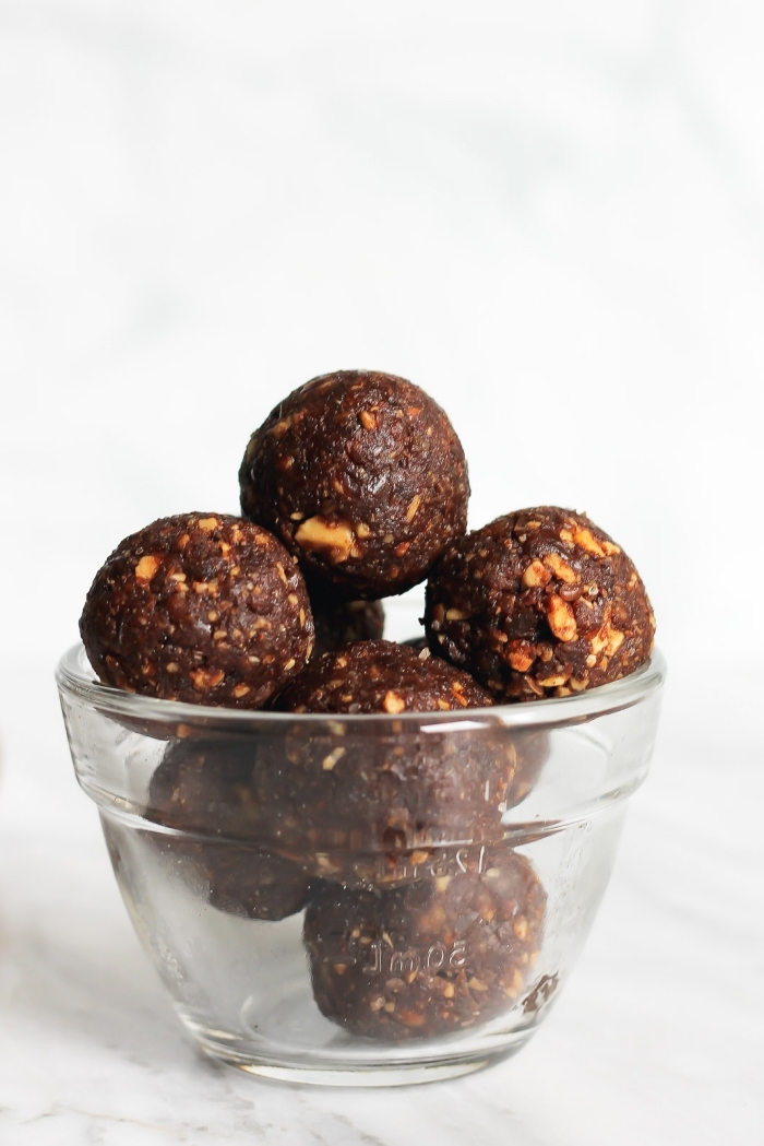white background, peanut butter energy balls, chocolate truffles, with nuts, in a glass bowl