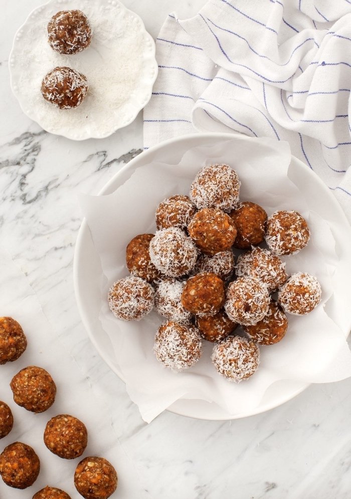 coconut flakes, in a white plate, peanut butter oatmeal balls, dipped in coconut flakes, white cloth