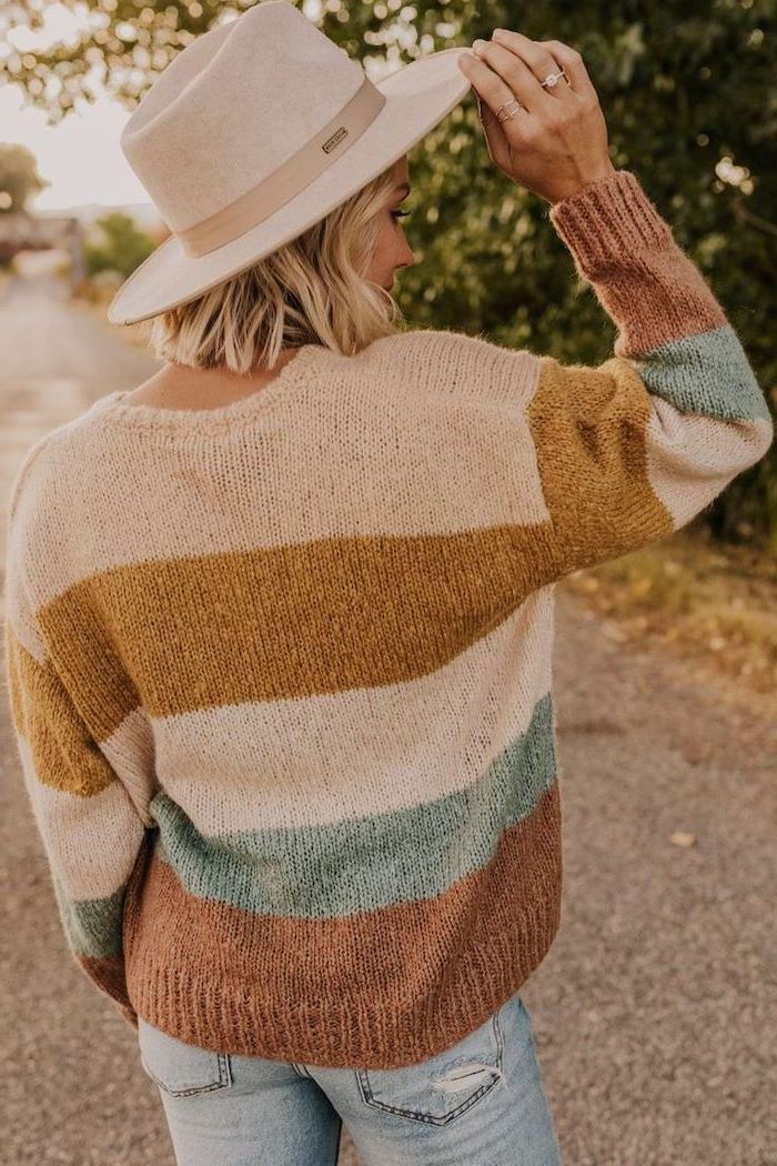 woman wearing a hat, colorful sweater and jeans, shoulder length layered hair, blonde wavy hair