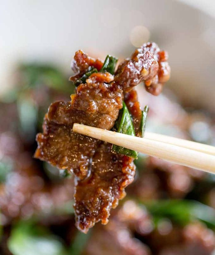 mpngolian beef, cut into pieces, held with chopsticks, what should i make for dinner, blurred background