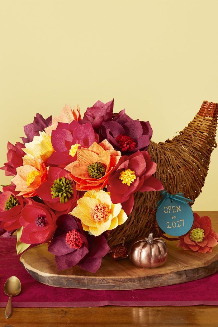 cornucopia with faux, paper flowers, thanksgiving decorating ideas, wooden log, red table runner