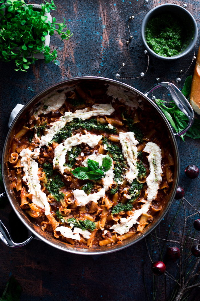creamy pesto lasagna, sauce on top, basil leaves for garnish, in a pot, easy healthy dinner ideas, black table