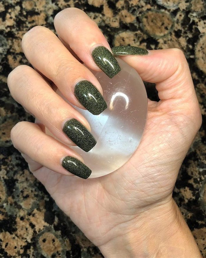 green glitter, nail polish, fall nail designs, hand holding a crystal ball, long square nails, granite countertop