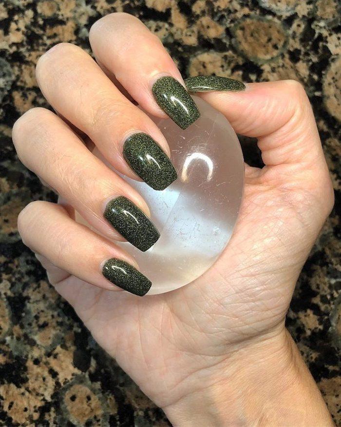 green glitter, nail polish, fall nail designs, hand holding a crystal ball, long square nails, granite countertop