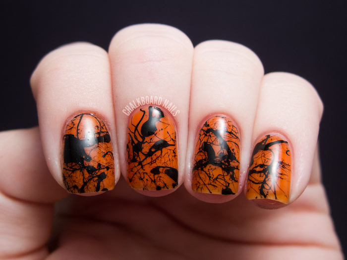 orange nail polish, black splashes, nail decorations, nail color ideas, black background, short squoval nails
