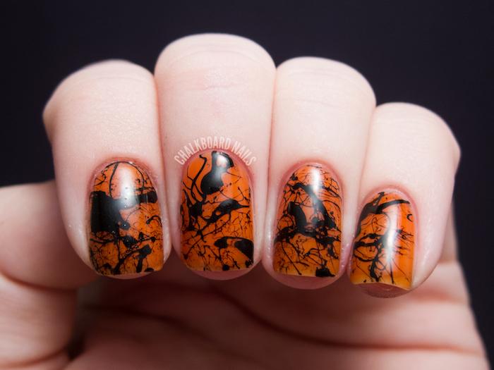 orange nail polish, black splashes, nail decorations, nail color ideas, black background, short squoval nails