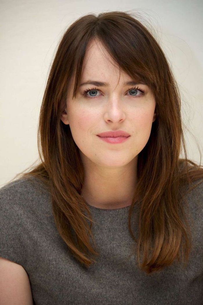 dakota johnson, wearing grey blouse, shoulder length layered hair, brown hair with side swept bangs