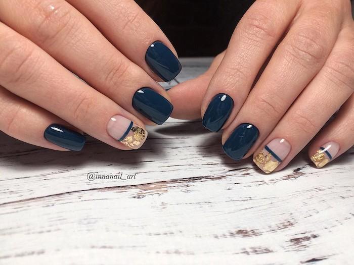 dark blue nail polish, gold glitter, nail decorations, nail color ideas, wooden table, short squoval nails