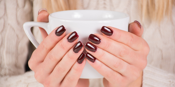 two hands, holding a coffee cup, burgundy red, nail polish, white sweater, cute nail colors, blonde hair