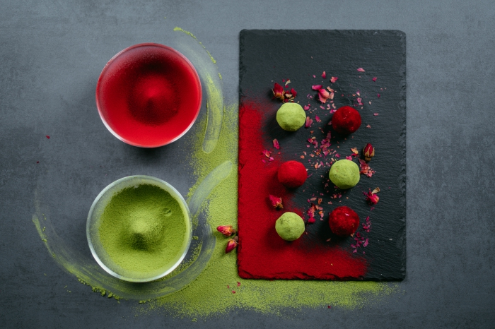 energy balls, cocoa in glass bowls, dyed in red and green, black cutting board, chocolate truffles