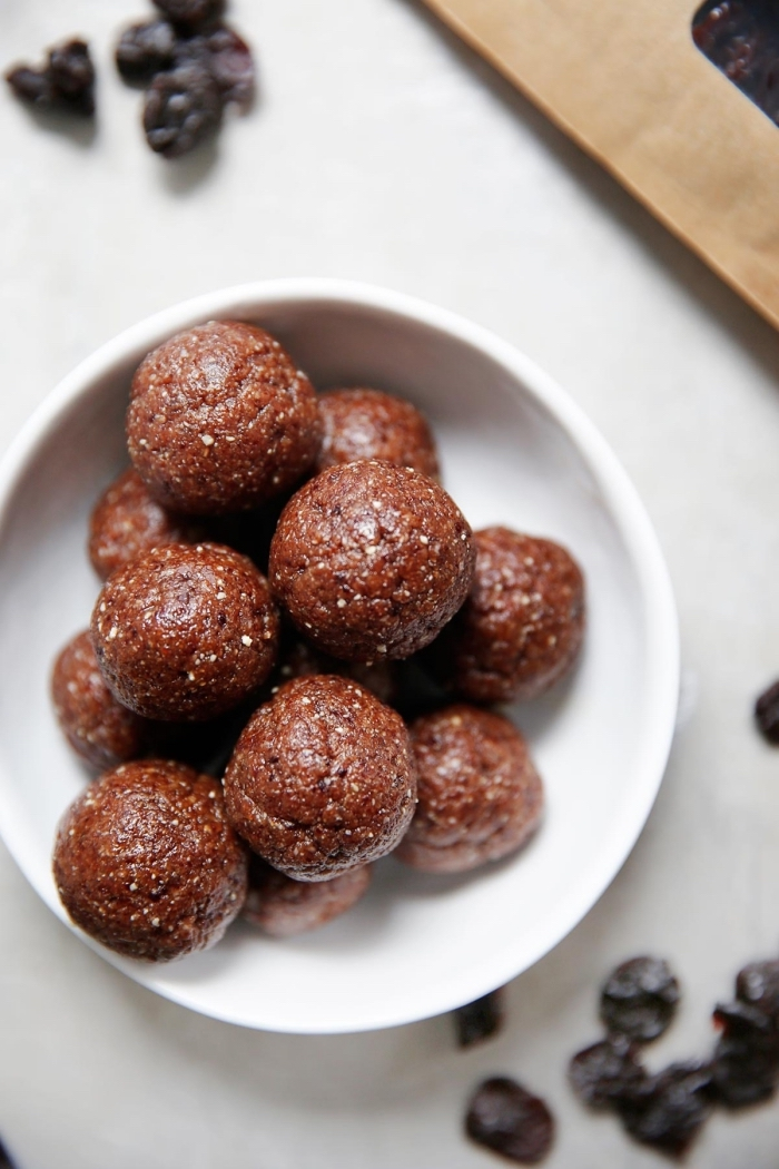dates scattered on the table, chocolate truffles, in a white bowl, peanut butter energy balls