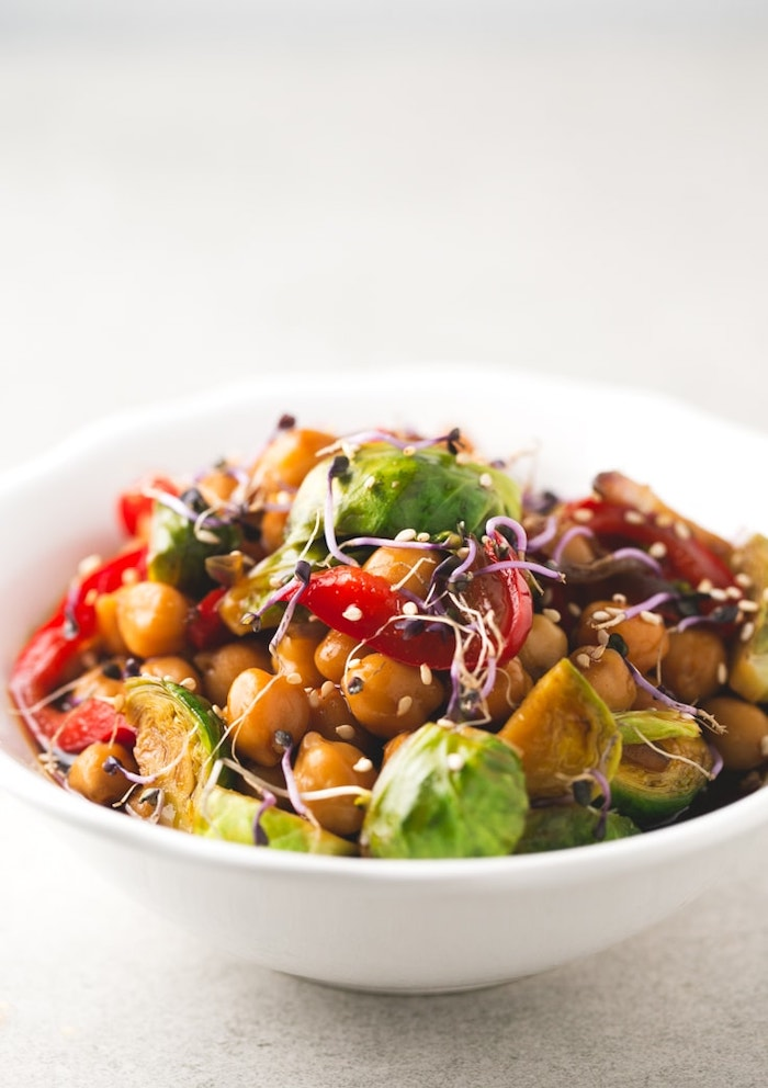 white ceramic bowl, healthy dinner ideas, chickpea and vegetables stir fry, with sesame seeds, white table