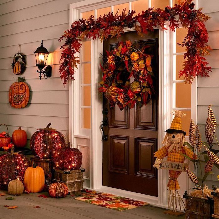 massive wooden door, wreath with autumn leaves, thanksgiving decorations diy, pumpkins arranged around it